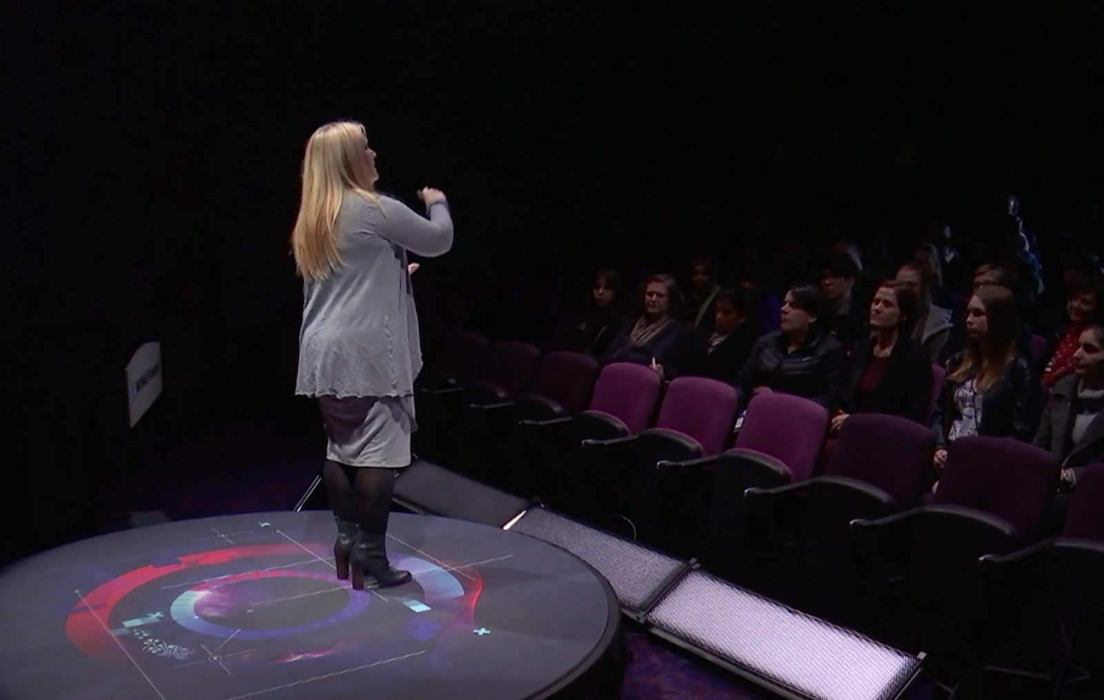 A female speaker at the Monash STEM Talks standing on a stage with a branded floor graphic